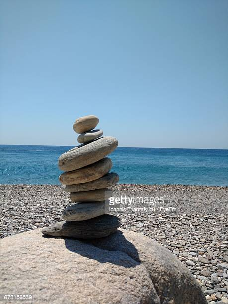 Stacked Pebbles On Shore Against Clear Sky