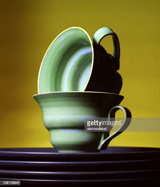 Stacked Teacups and Plates on Yellow Background