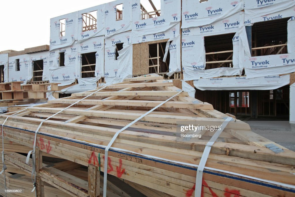 Stacked trusses sit behind new Lexington Homes LLC townhomes under construction in Des Plaines, Illinois, U.S., on Monday, Jan. 14, 2013. The U.S. Census Bureau is scheduled to release housing starts figures on Jan. 17. Photographer: Tim Boyle/Bloomberg via Getty Images