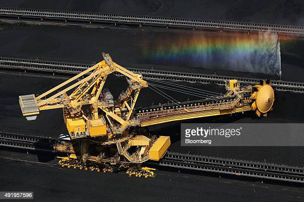 A stackerreclaimer operates next to stockpiles of coal as a rainbow forms in a spraying jet of water at the Newcastle Coal Terminal in this aerial...