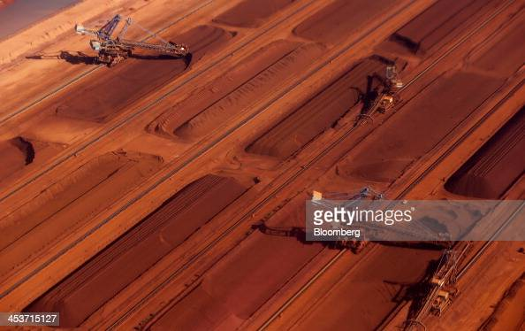 Stackers operate next to stockpiles of iron ore at the processing facility at Fortescue Metals Group Ltd's Herb Elliott Port in Port Hedland in the...