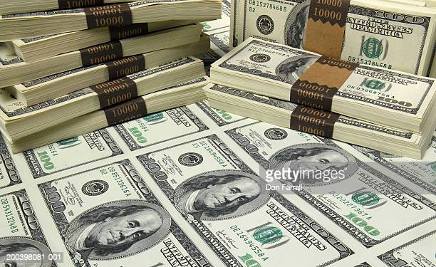 Stacks and sheet of US one hundred dollar bills, elevated view