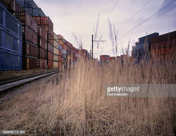 Stacks of cargo containers and train tracks, (multiple exposure)