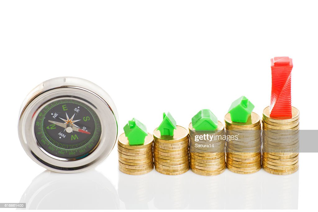 Stacks of coins, green and red home with compass. : Stock Photo