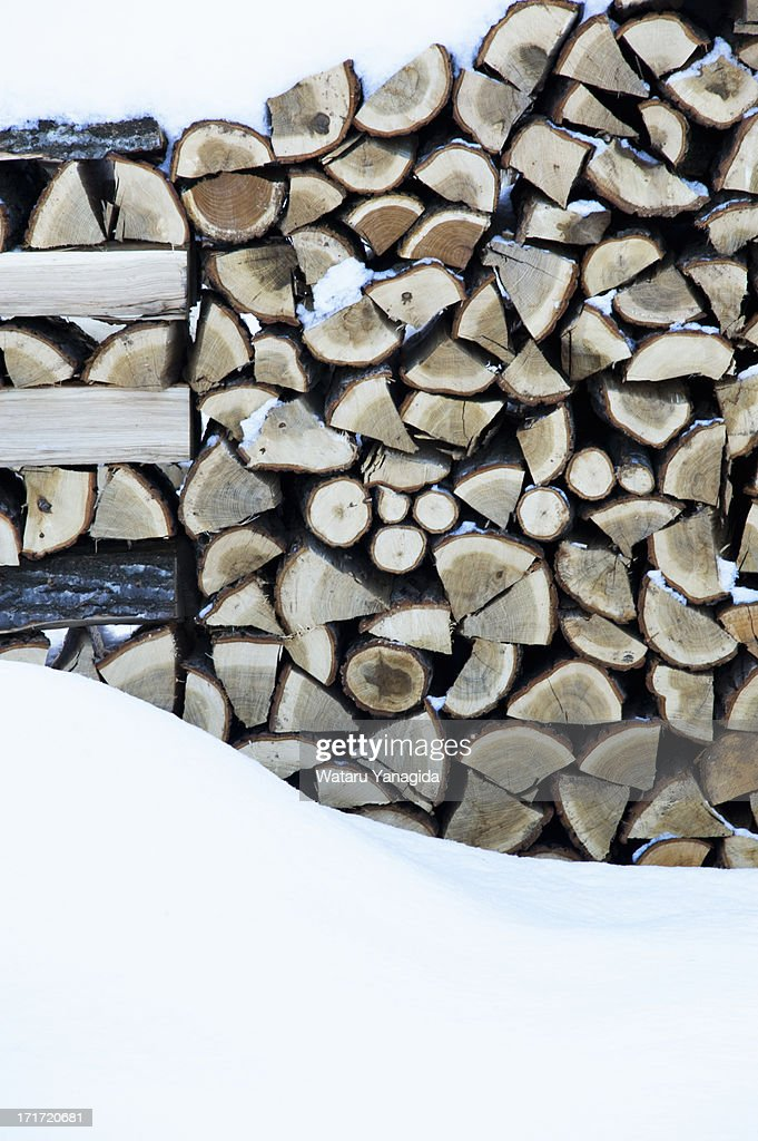 Stacks of firewood covered with snow : Stock Photo