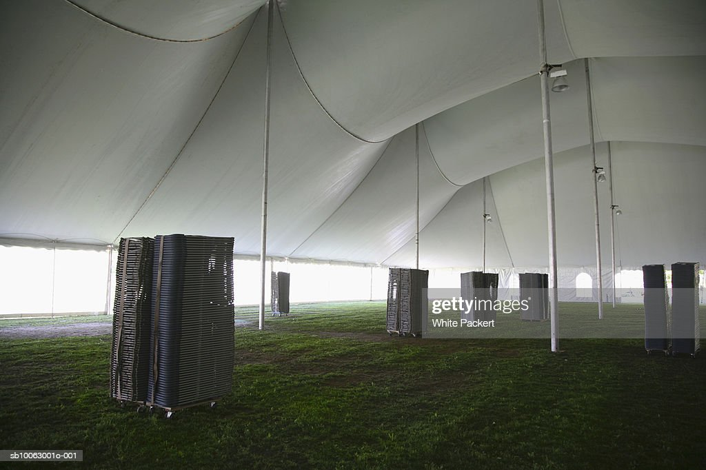 Stacks of folding chairs inside marquee : Stock Photo