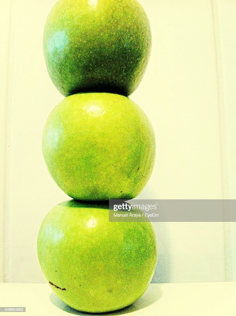 Stacks Of Granny Smith Apples Against White Wall
