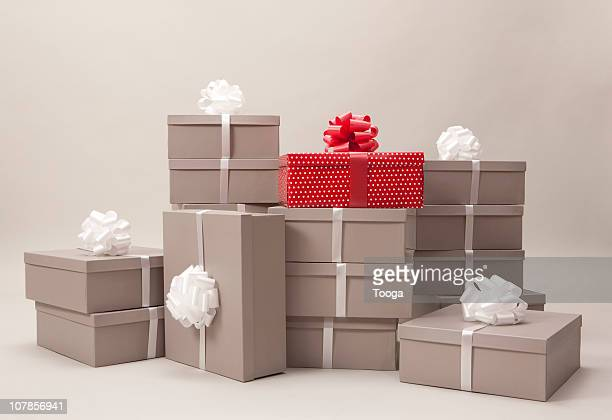 Stacks of gray boxes and one red package with bows