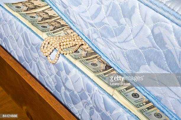 stacks of money and pearls under mattress