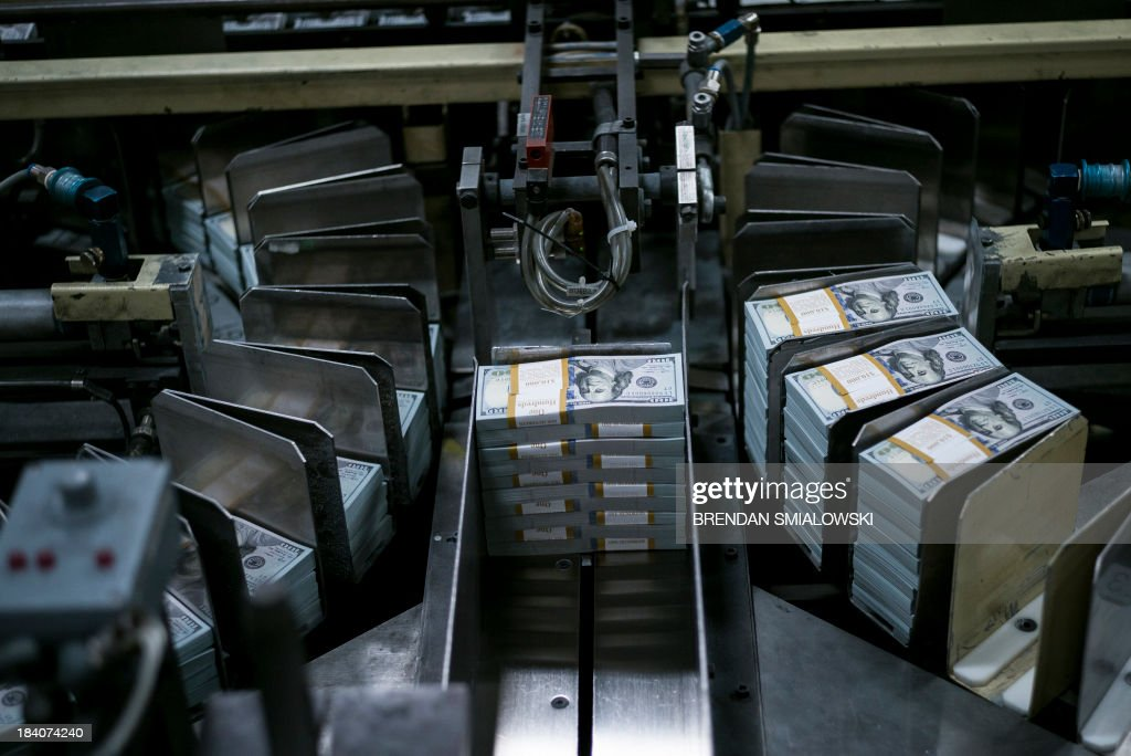 Stacks of money move through a machine during the phase of production where the new 100 USD bills are applied with a serial number, a US Federal Reserve seal, are cut and stacked at the US Bureau of Engraving and Printing's Western Currency Facility October 11, 2013 in Fort Worth, Texas. The facility is currently the sole producer of the new 100 USD bill. The bill went into circulation on October 8 and includes new security features such as a purple band with moving images, ink that changes color with the angle as well as a new more colorful design.