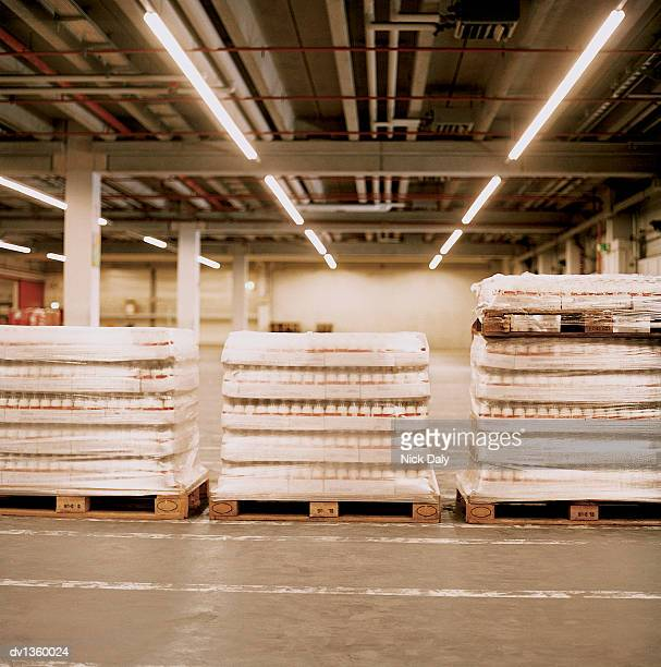 Stacks of Packaged Milk Bottles on Pallets in a Factory