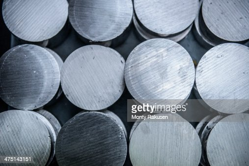 Stacks of raw and unworked steel discs in factory, overhead view