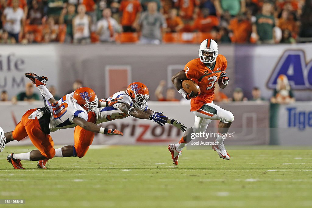 Stacy Coley #3 of the Miami Hurricanes runs with the ball and eludes the attempted tackle by two Savannah State Tigers on September 21, 2013 at Sun Life Stadium in Miami Gardens, Florida. Miami defeated Savannah State 77-7.