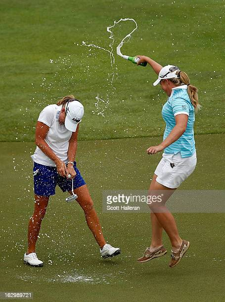 Stacy Lewis of the USA is sprayed with beer by Brittany Lincicome after Lewis won the HSBC Women's Champions at the Sentosa Golf Club on March 3 2013...