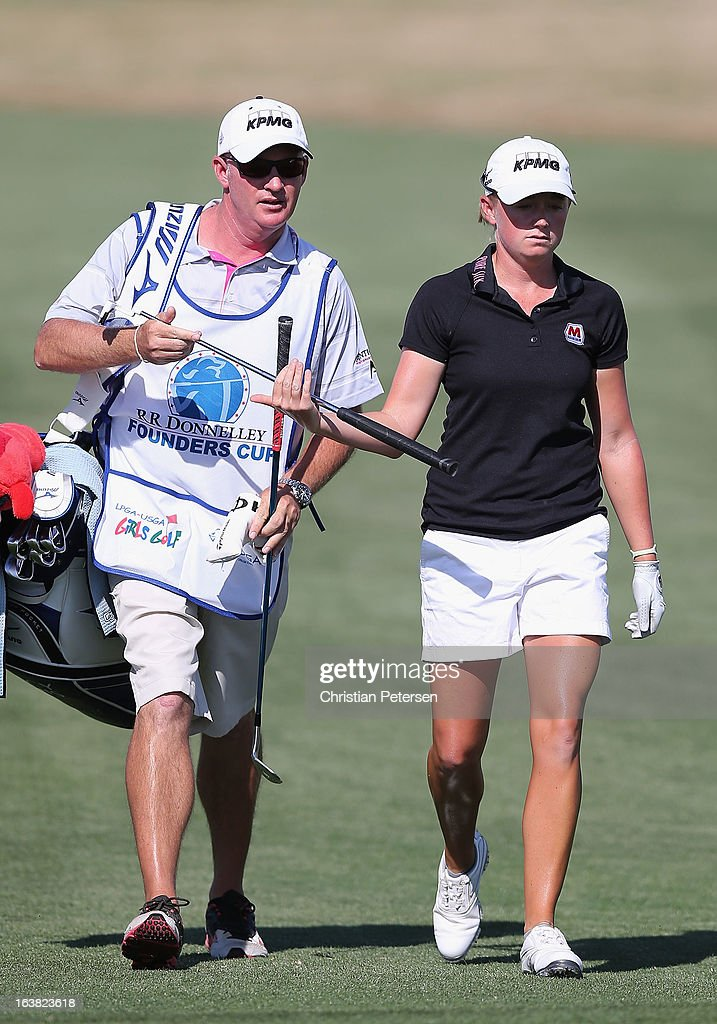 <a gi-track='captionPersonalityLinkClicked' href=/galleries/search?phrase=Stacy+Lewis+-+Golfer&family=editorial&specificpeople=4217318 ng-click='$event.stopPropagation()'>Stacy Lewis</a> (R) takes a putter from her caddie <a gi-track='captionPersonalityLinkClicked' href=/galleries/search?phrase=Travis+Wilson+-+Golf+Caddy&family=editorial&specificpeople=15147345 ng-click='$event.stopPropagation()'>Travis Wilson</a> as they walk down the 15th hole during the third round of the RR Donnelley LPGA Founders Cup at Wildfire Golf Club on March 16, 2013 in Phoenix, Arizona.