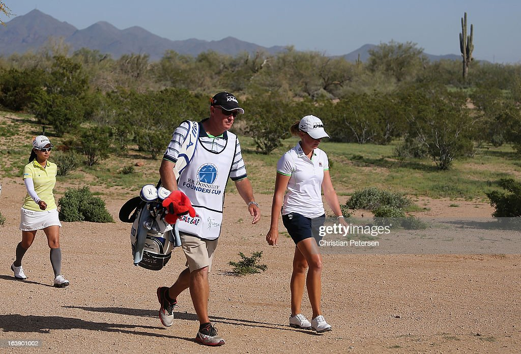 Stacy Lewis, Travis Wilson and Ai Miyazato of Japan walk down the 18th hole during the final round of the RR Donnelley LPGA Founders Cup at Wildfire Golf Club on March 17, 2013 in Phoenix, Arizona.