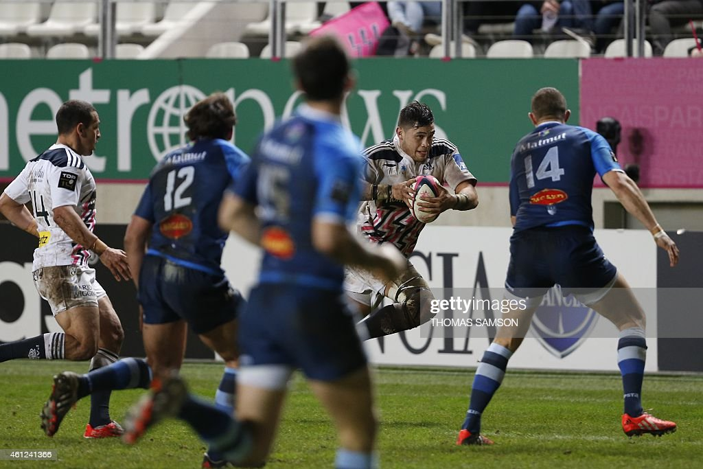 Stade Francais' French number eight <a gi-track='captionPersonalityLinkClicked' href=/galleries/search?phrase=Raphael+Lakafia&family=editorial&specificpeople=7183172 ng-click='$event.stopPropagation()'>Raphael Lakafia</a> (C) runs with the ball during the French Top 14 rugby union match between Stade Francais Paris and Castres Olympique on January 9, 2015 at the Jean Bouin stadium in Paris. AFP PHOTO / THOMAS SAMSON