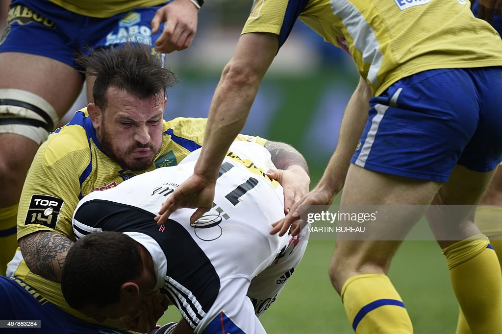Stade Francais Paris' French winger Julien Arias (C) is tackled by Clermont's French prop <a gi-track='captionPersonalityLinkClicked' href=/galleries/search?phrase=Thomas+Domingo&family=editorial&specificpeople=4651174 ng-click='$event.stopPropagation()'>Thomas Domingo</a> (L) during the French Top 14 rugby match between Stade Francais Paris and ASM Clermont Auvergne at Jean Bouin stadium in Paris on March 28, 2015.