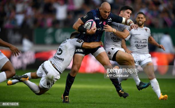 Stade Francais Paris' Italian Number Eight Sergio Parisse is tackled by RC Toulon's French lock Romain Taofifenua during the French Top 14 rugby...