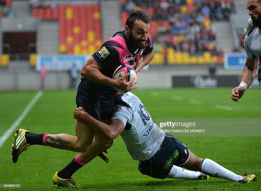 Stade Francais Paris' Jeremy Sinzelle (L) is tackled after the French Top 14 rugby union match between Agen and Stade Français on May 28, 2016 at the MMArena Stadium in Le Mans, northwestern France.