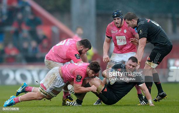 Stade Francais Paris's French prop Rabah Slimani and Stade Francais Paris's South African flanker Jonathan Ross tackle Munster's Dave Kilcoyne during...