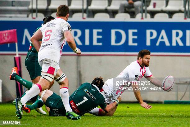 Stade Francais South African Craig Burden is tackled by Paus French Prop Jeremy Hurou during the French Top 14 rugby union match between Stade...