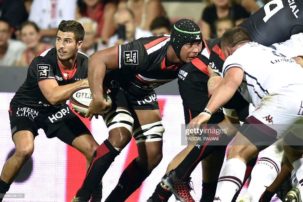 Stade Toulousain's French flanker Thierry Dusautoir passes the ball to his teammate French scrumhalf Sebastien Bezy during the French Top 14 Rugby...