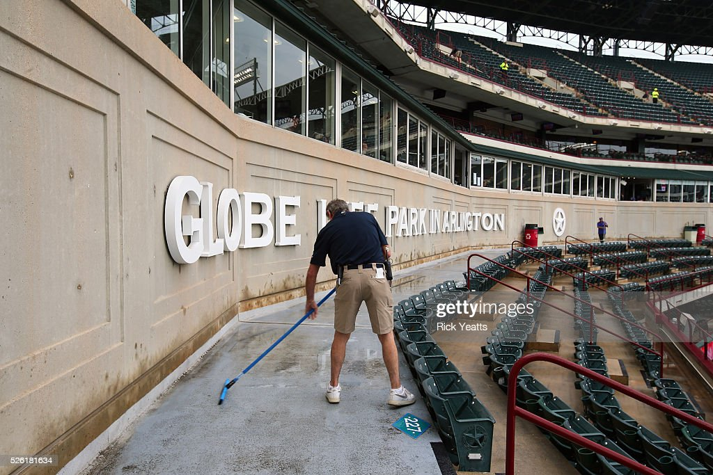 Stadium crew sweep water from the walkways before the start of the game between the Los Angeles Angels of Anaheim and the Texas Rangers at Global Life Park in Arlington on April 29, 2015 in Arlington, Texas.