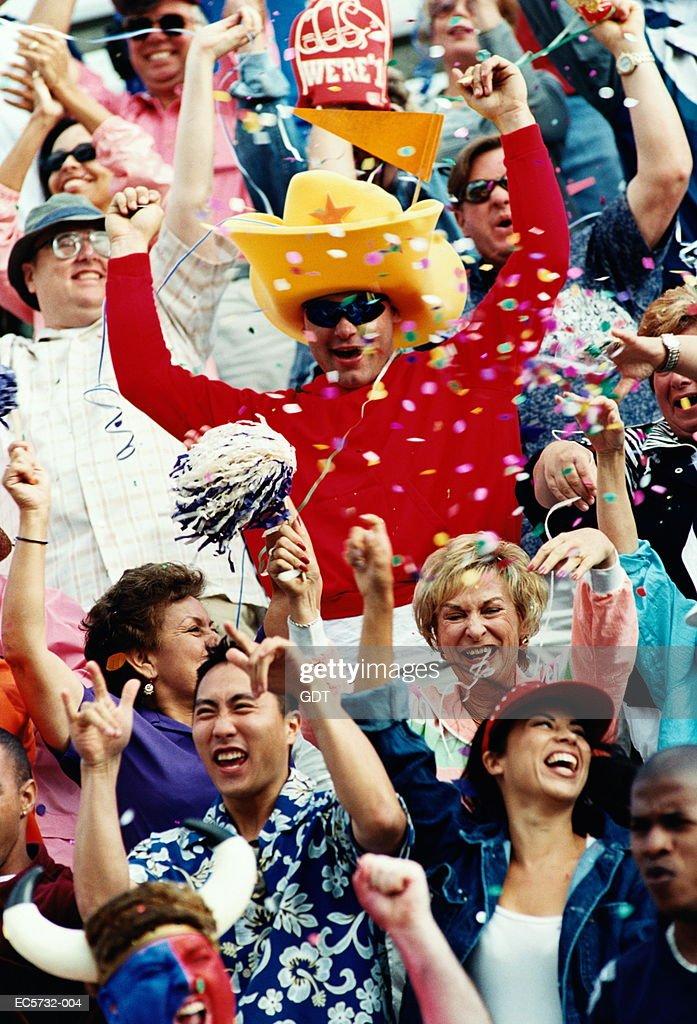 Stadium crowd celebrating, man wearing yellow hat : Stock Photo