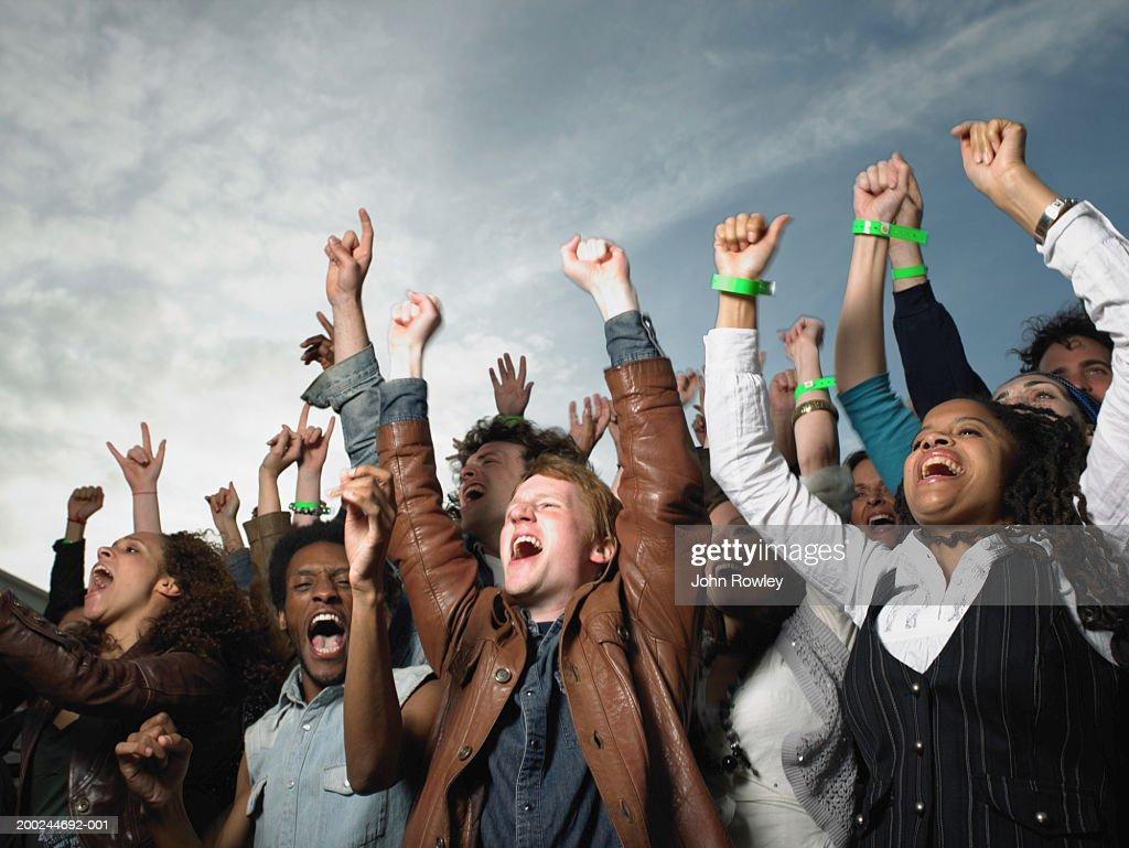 Stadium crowd cheering, arms raised, low angle view : Stock Photo