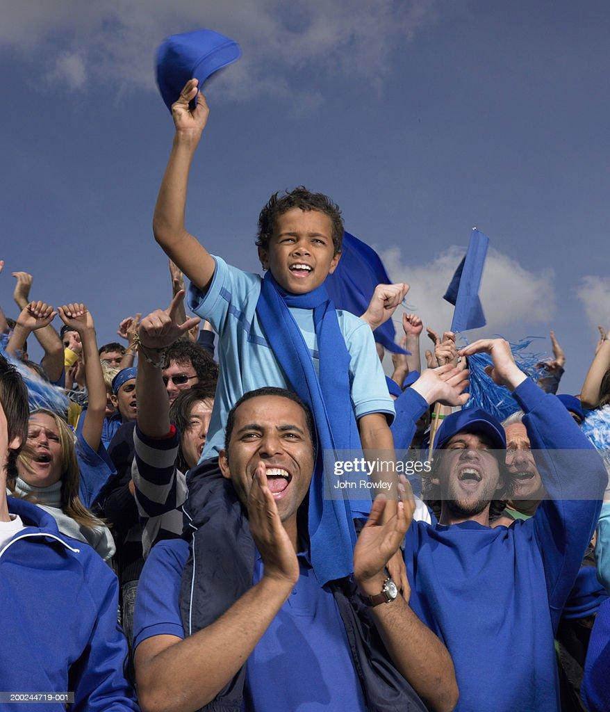 Stadium crowd cheering, boy (5-7) on father's shoulders, waving cap : Stock Photo