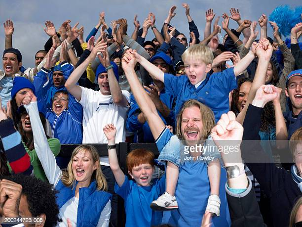 Stadium crowd cheering, boy (4-6) sitting on father's shoulders