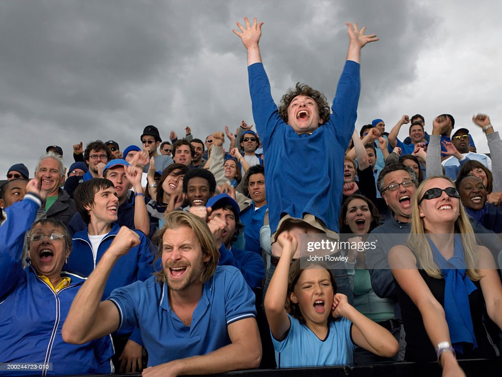 Stadium crowd cheering, one man jumping high, low angle view : Stock Photo
