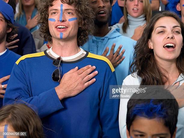 Stadion-crowd, fans singen mit Händen, die über Herz, Nahaufnahme