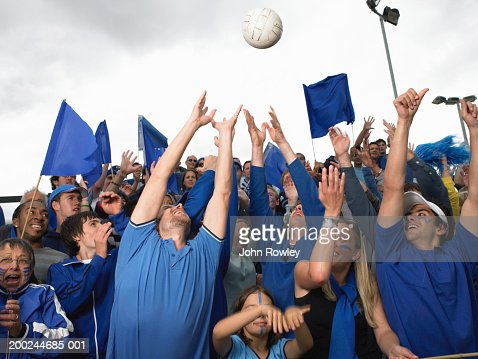 Stadium crowd reaching for ball sailing overhead : Stock Photo