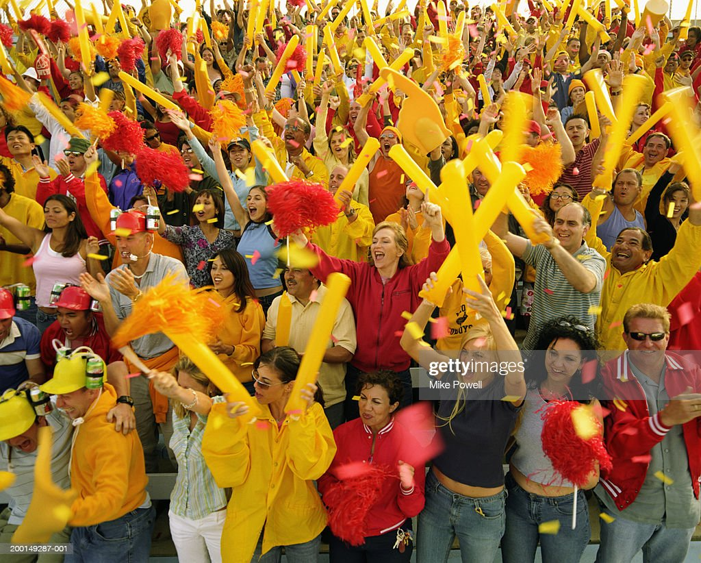Stadium crowd waving cheering sticks and pom poms in air : Stock Photo