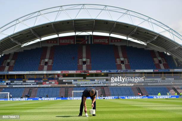 A stadium employee freshens the lines on the pitch prior to the English Premier League football match between Huddersfield Town and Newcastle United...