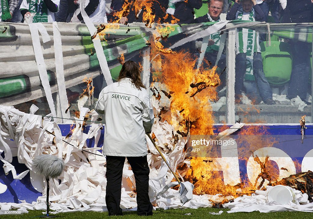 A stadium employee removes burning papers after supporters allegedly set fire in the stadium of FC Groningen prior to the match FC Groningen vs Ajax...