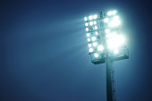 Stadium lights against dark blue sky  - front view