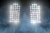 stadium lights and smoke against dark night sky background