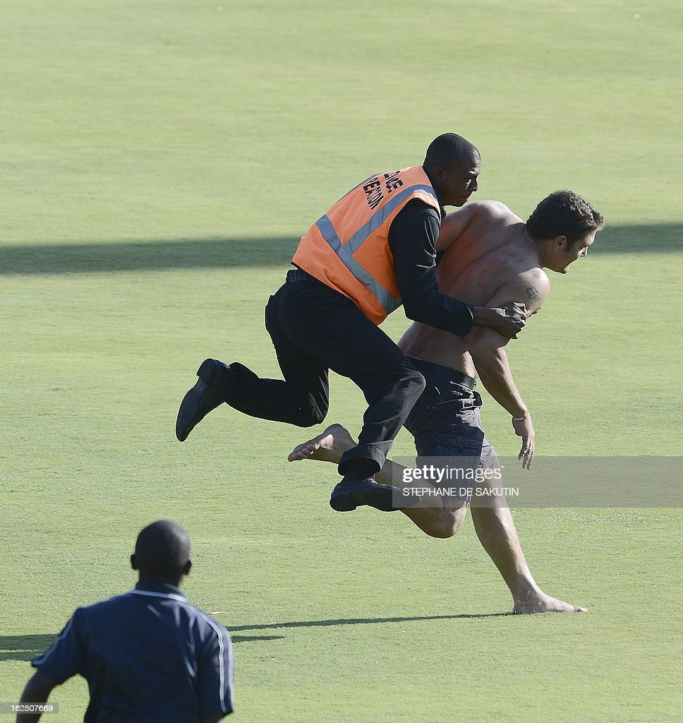 Stadium security tries to stop a man running on the pitch during the third day of the third Test match between South Africa and Pakistan on February 24, 2013 at Super Sport Park in Centurion.