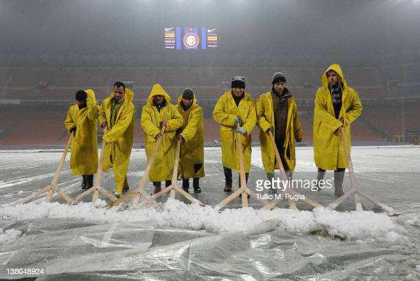 Stadium staff remove snow from the pitch in preparation for the Serie A match between FC Internazionale Milano and US Citta di Palermo at Stadio...