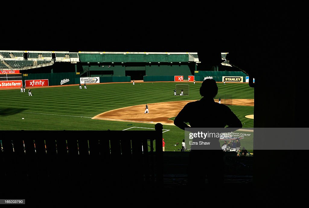 A stadium worker watches the Oakland Athletics take batting practice before their game against the Seattle Mariners on Opening Day at O.co Coliseum on April 1, 2013 in Oakland, California.