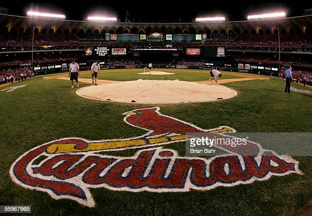 Stadium workers cover home plate with a tarp as security keeps a close eye on fans remaining in the stands following the St Louis Cardinals 51 loss...