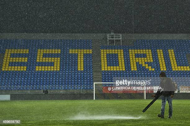 A stadium's employee tries to remove water from the pitch under heavy rain during the UEFA Europa League Group E football match Estoril Praia vs PSV...