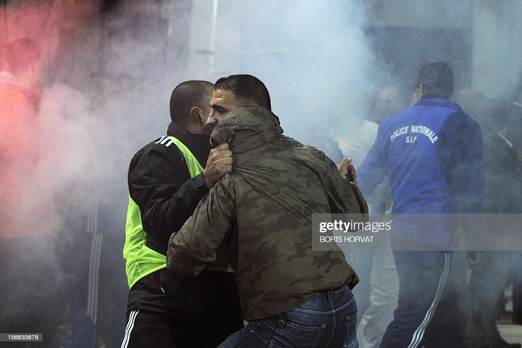 A stadium's security employee stops a Fenerbahce's fan (R) during the UEFA Europa League Group C3 football match between Olympique de Marseille and Fenerbahce SK, on November 22, 2012, at the velodrome stadium in Marseille. AFP PHOTO / BORIS HORVAT