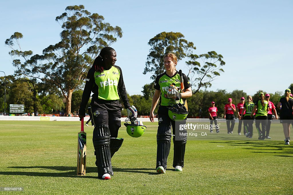 Stafanie Taylor (L) of the Thunder and Alex Blackwell (R) of the Thunder walk from the field after winning the Women's Big Bash League match between the Sydney Thunder and the Sydney Sixers at Howell Oval on December 6, 2015 in Sydney, Australia.