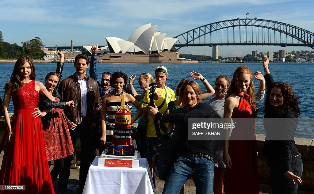 Staff alongside wax figures of Australian celebrities celebrate the first anniversary of Madame Tussauds Sydney in front of the Harbour Bridge and the Opera House in Sydney on April 17, 2013. Madame Tussauds Sydney organised a birthday party with wax figures of Australian celebrities including Nicole Kidman, Keith Urban, Dannii Minogue, Miranda Kerr, Eric Bana and Lleyton Hewitt. AFP PHOTO / Saeed Khan