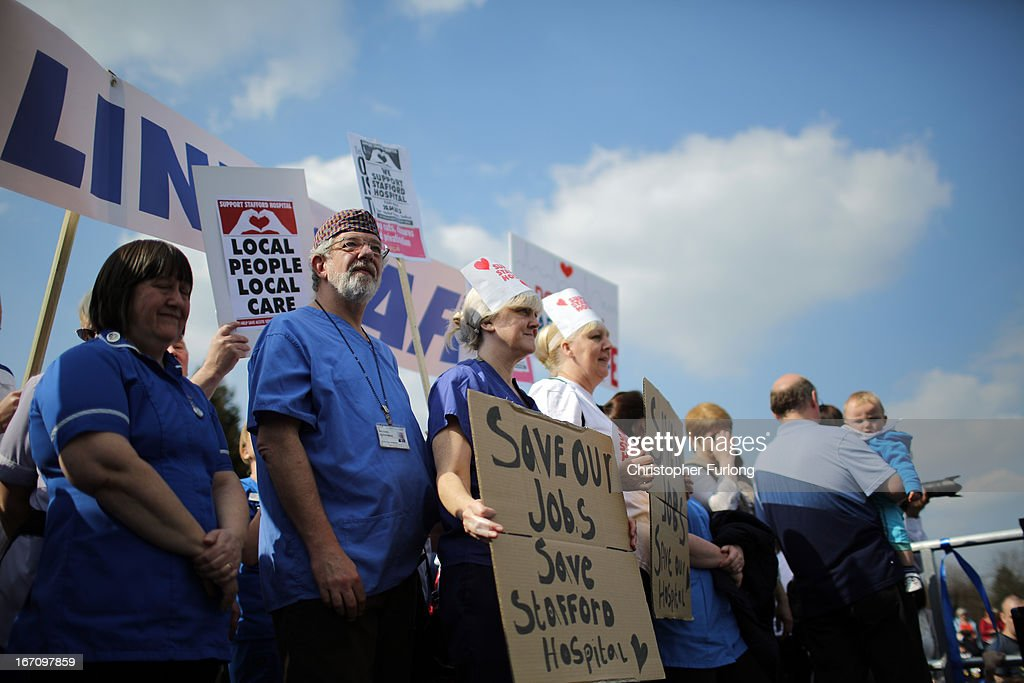 NHS staff and campaigners hold signs as they rally outside Stafford Hospital as they demonstrate to keep major health services at the scandal hit Stafford Hospital on April 20, 2013 in Stafford, England. The march was organised by the Support Stafford Hospital campaign group who are fighting cuts to major health services at the hospital. The Health regulator monitor has appointed two special administrators to produce a plan for the reorganisation of future services.