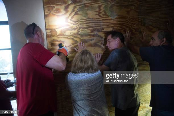 Staff and guests board up the front of a hotel after it blew open in Bonita Springs Florida northeast of Naples on September 10 2017 as Hurricane...